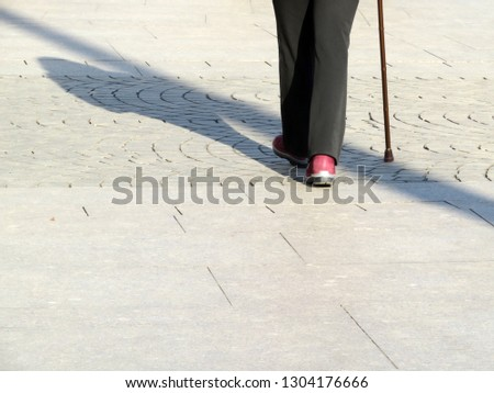 Woman walking with a cane on the street, long shadow on pavement. Concept of elderly people, blind person, limping, diseases of the spine