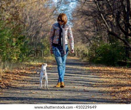woman walking with a dog in...