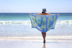 Woman walking with a towel around her on a pristine beach with the word