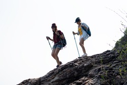 Woman walking with a walking stick in the mountains.