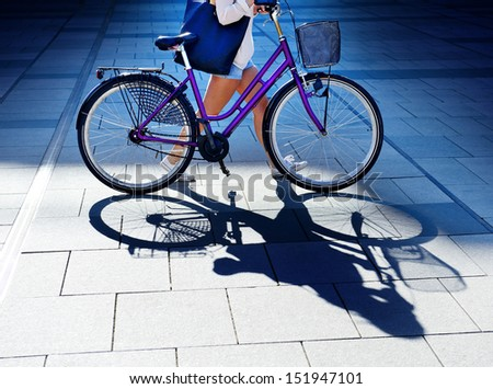 Woman walking with bike in evening