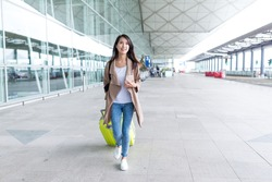 Woman walking with her luggage in airport