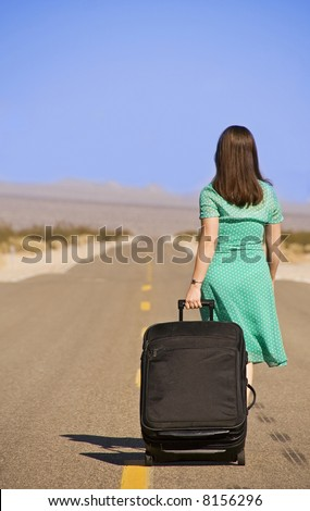 Woman walking with suitcase on empty road, California