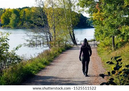 Woman walks on walking path at seaside on autumn day. Location: Ruissalo island, Turku, Finland.