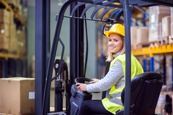Woman warehouse worker with forklift.