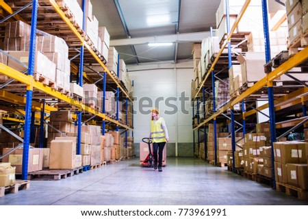 Woman warehouse worker with hand forklift truck. #773961991