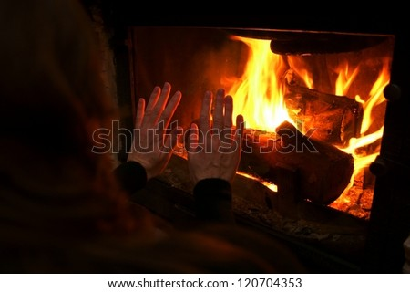 Woman  warm up by the fire / fireplace
