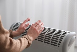 Woman warming hands near electric heater at home, closeup