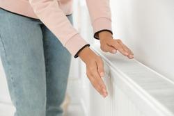 Woman warming hands on heating radiator near white wall, closeup