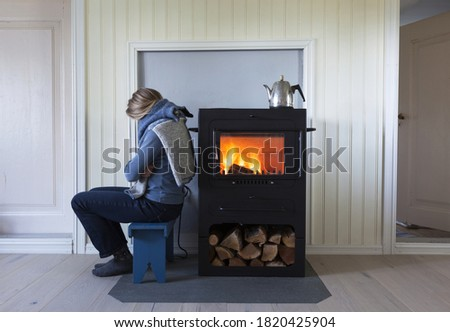Woman warming herself by the side of metal stove; fire burning in stove, firewood under stove and coffee pot on stove.