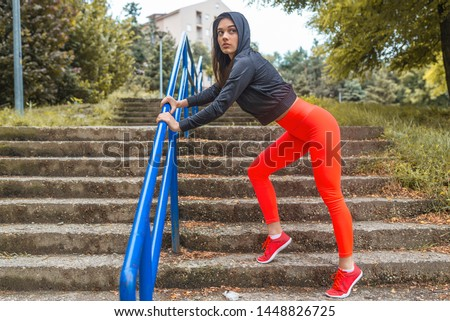 Woman warming up before jogging. Woman athlete stretching in the park before running. Sporty young woman. Young woman stretching leg after running