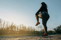 Woman warming up legs before outdoor running. Getting ready for morning jogging. Sport, activity, healthy lifestyle and weight losing