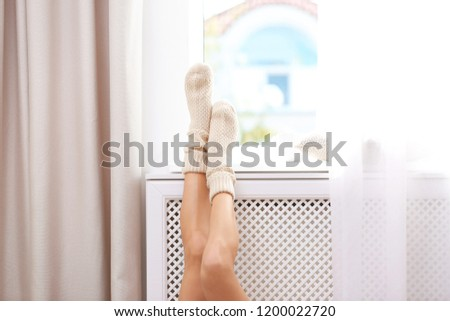 Woman warming up with feet on heater near window #1200022720