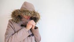 Woman warms up freezing hands by blowing hot air dressed in warm coat with a hood over her head. Copy space for text.