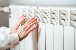 Woman warms up hands over heater. Concept of the need for good central heating.