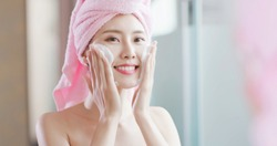 woman wash her face in the bathroom after shower