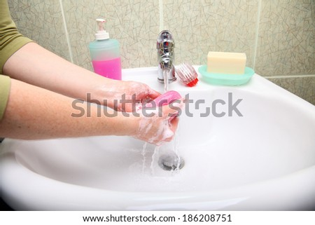 Woman wash red soapy hands in bathroom soap