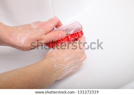 Woman wash red soapy hands in bathroom soap nail brush person scrubbing nails