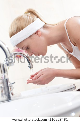 Woman washes her face in bathroom