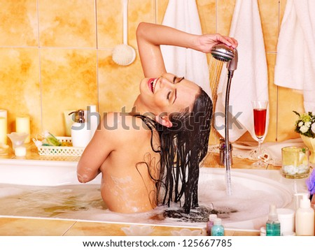 Woman washes her head at home bathroom.