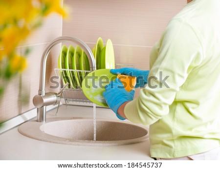 Woman Washing Dishes. Kitchen. Dishwashing. Woman doing housework at home