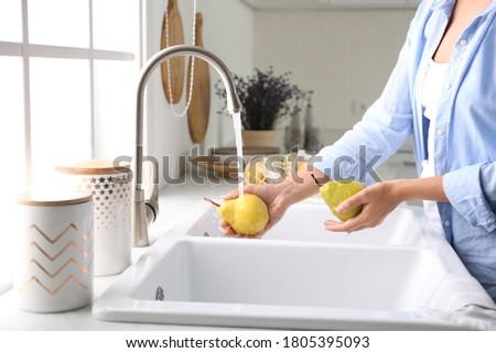 Woman washing fresh ripe pears in kitchen, closeup Photo stock ©