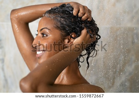 Woman washing hair showering in bathroom at home. Smiling black woman bathing while looking away. Happy woman rinsing hair while taking a shower at luxury spa.