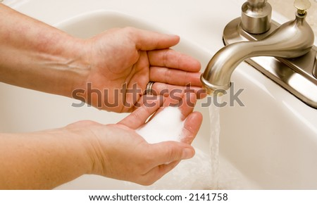 woman washing hand under running water white sink chrome spout