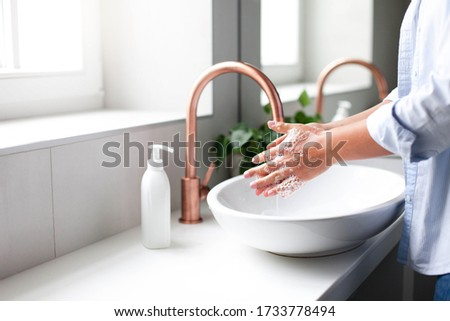Woman washing hands under water tap. Self care and hygiene. Close up of female hand. Infection prevention. Liquid antibacterial soap and foam. Step by step instruction. Step 2.