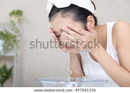 Woman washing her face #497641336