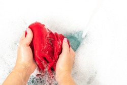 Woman washing red color clothes with detergent foam