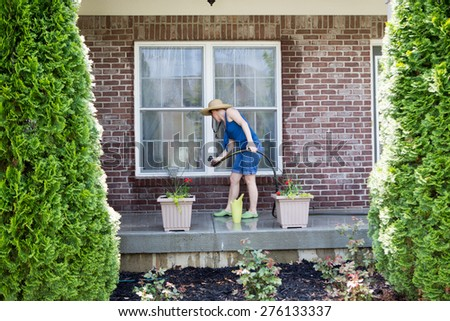 Woman washing the exterior windows of a house with an attachment on a hose as she cleans and refreshes the house after winter for the new spring season, view framed by two evergreen cypresses
