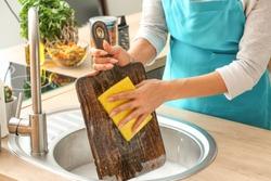 Woman washing wooden board in kitchen sink