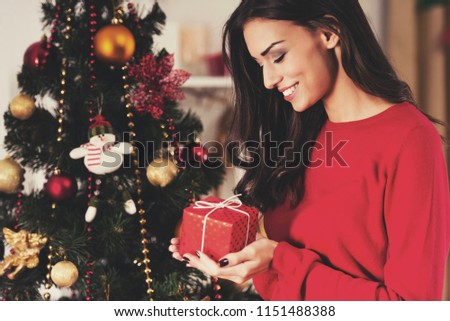 Woman Watch at Christmas Present. Portrait of Young female. Preparations for Celebration. Happiness at Home. Profile View. Holiday Concept. Caucasian Young Woman. Decorating Christmas Tree.