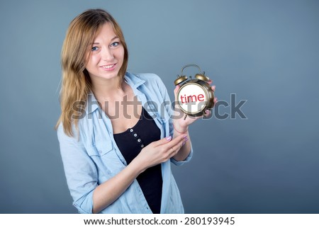 Woman watches and time. Woman holding a clock. Young modern girl on a blue background. Ordinary young european girl with an alarm clock in his hands. Girl student indicates the time on the clock.