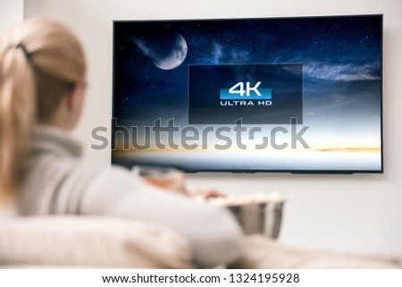 Photo of  Woman watches tv with 8k ultra hd resolution. Picture on the screen created in graphic software.