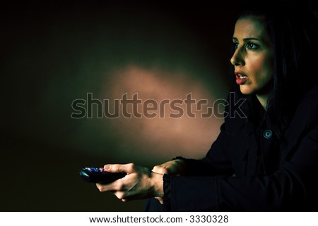 Woman watching a scary movie on TV