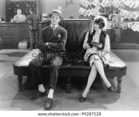 Woman watching a sleeping man on a leather couch - stock photo
