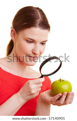 Woman watching green apple with a magnifying glass