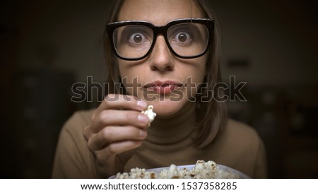 Woman watching movies and eating popcorn, she is addicted and glued to the screen
