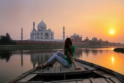 Woman watching sunset over Taj Mahal from a boat, Agra, India. It was build in 1632 by Emperor Shah Jahan as a memorial for his second wife Mumtaz Mahal.