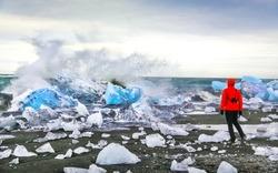 Woman watching waves crash against icebergs at Jokulsarlon glacial lagoon near Vatnajokull National Park, southeast Iceland