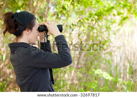 woman watching wildlife in park with binoculars