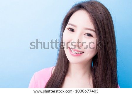 woman wear brace look you and smile happily on the blue background #1030677403