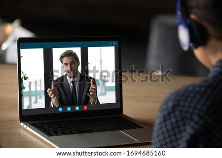 Woman wear headphones listen tutor during online class pc screen view over trainee shoulder. Colleague express opinion share ideas working together on project using video call, e-learn e-coach concept