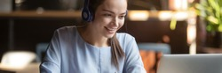 Woman wear headphones look at pc enjoy study online with tutor, listen audio lecture watch webinar prepare for exams, e-learn, self education concept. Horizontal photo banner for website header design