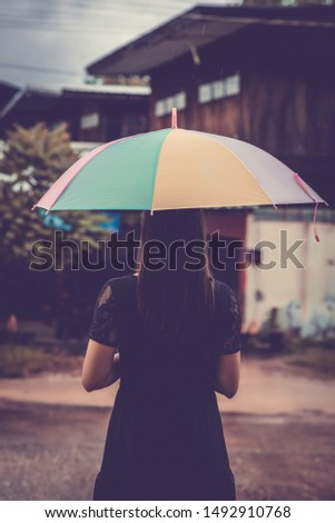 Woman wearing a black shirt holding umbrella while raining. Lonely and lonely concept.