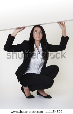 woman wearing a business suit in a tight spot with the ceiling right above her squashing her down