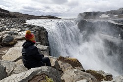 Woman wearing a coat and a woolly hat watching Dettifoss waterfall, ICELAND: the most powerful waterfall in Europe.