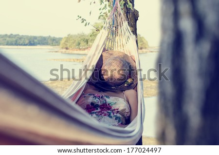 Stock Photo Woman wearing a dress with floral pattern and covering her face with a straw hat while relaxing in a hammock outdoors, in a warm day of summer, next to a sea and a green area. With retro effect.